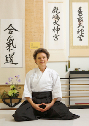 Dr. Myriam Hunink, PhD, meditates in her aikido clothes in the dojo