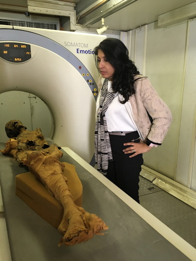 Dr. Sahar Saleem looks closely at the mummy on the CT scanner table