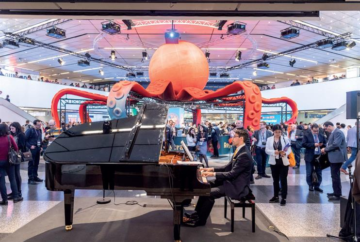 Large octopus sculpture behind man playing piano
