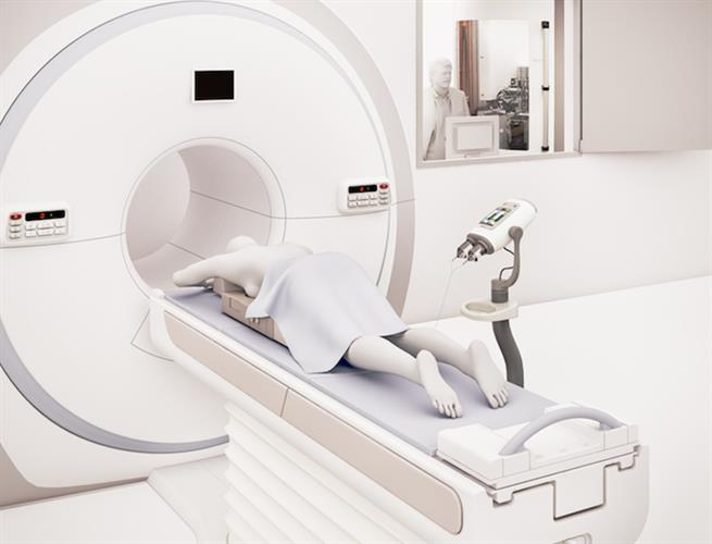 The scanner room showing a patient positioned in the MR scanner and the SPINlab hyperpolarizer in the room next door