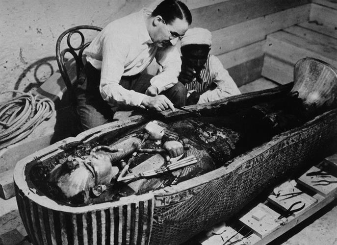 Howard Carter and an Egyptian workman examining the third coffin of Tutankhamun